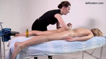 يقوم بتدليك علاجي لامرأة شابة عارية مستلقية على طاولة التدليك ولكن في نفس الوقت